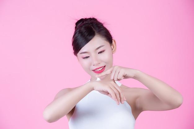 ピンク色の背景上の肌にクリームと美しい女性。