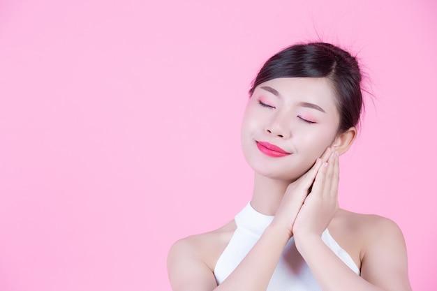 健康的な肌とピンクの背景の美しさを持つ美しい女性。