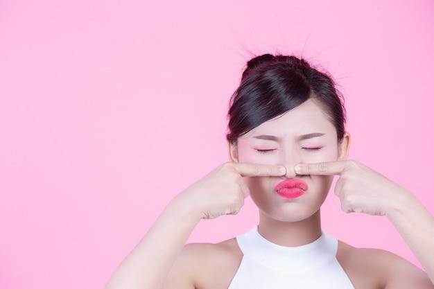 顔の皮膚の問題の女性 - 不幸な若い女性がピンクの背景に彼女の肌に触れます。