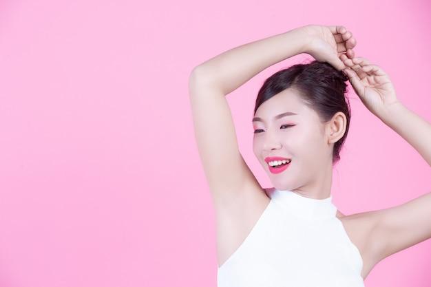 ファッションの女の子はピンクの背景に手のジェスチャーでドレスアップ。