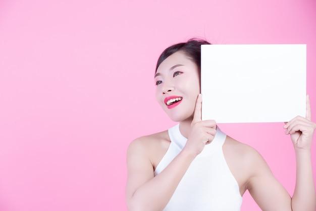 Красивая женщина держа лист белой доски на розовой предпосылке.