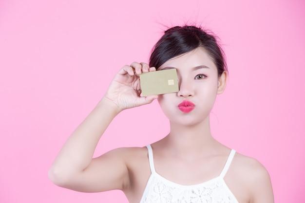 Красивая женщина, держащая карты на розовом фоне.