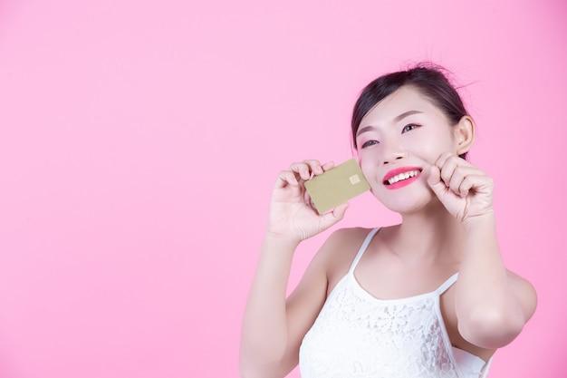 ピンクの背景にカードを保持している美しい女性。