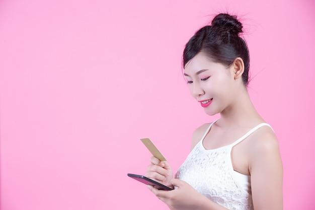 ピンクの背景にスマートフォンとカードを保持している美しい女性