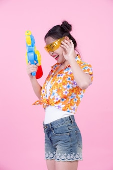 ピンクの背景の水鉄砲を持って幸せな女の子。