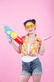 Счастливая девушка держа розовый водяной пистолет предпосылки.