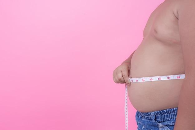 ピンク色の背景に太りすぎの肥満の男の子。