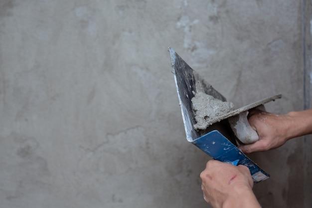Штукатур ремонтирует внутренние стены.