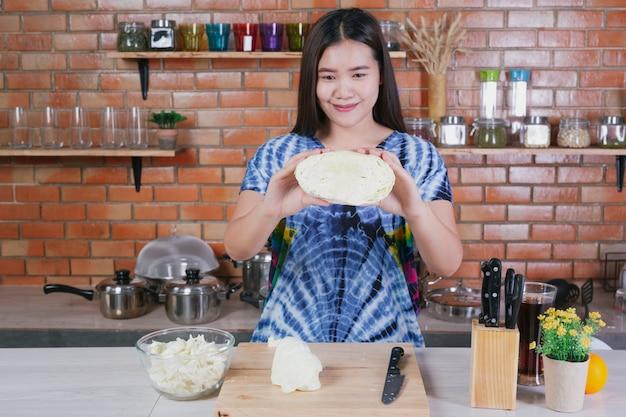 美しい女性が自宅の台所で野菜を切っています。