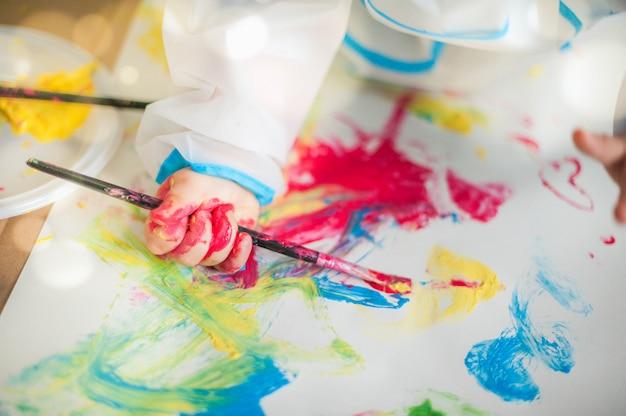 ブラシ、パレット、塗装中の子供の小さな手のクローズアップ
