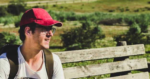 Молодой человек в красной шапочке сидит на деревянной скамейке