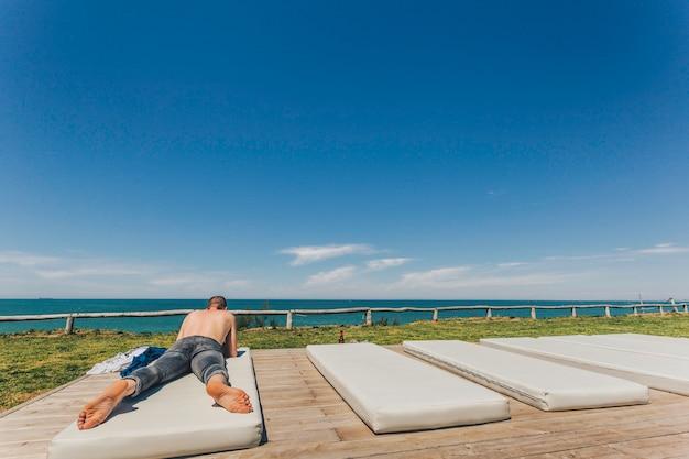Кавказский молодой человек без рубашки и в джинсах, лежа на пляже на белом матрасе
