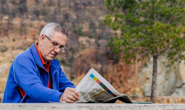 Старший мужчина в очках читает газету в парке, вид сбоку
