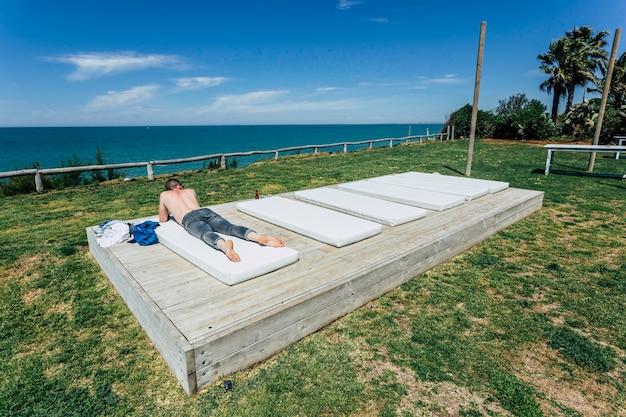 白人の若い男が上半身裸で、ビーチに横になってジーンズ