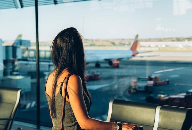 彼の飛行を待っている空港で荷物見て窓のそばに立っている女性観光客。