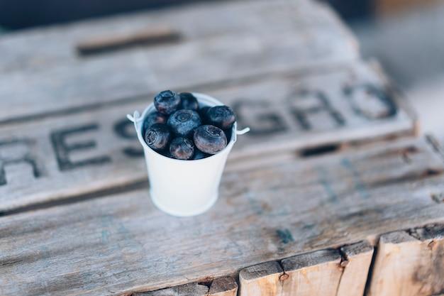 木材と金属製のボウルでジューシーで健康的なブルーベリーのクローズアップビュー。新鮮さと自然の朝食または軽食。