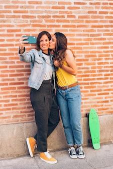 Две женщины целуются и делают селфи. понятие терпимости и однополых отношений.