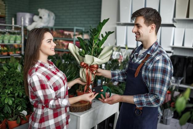 お祝いラッパーで植木鉢を購入することを決定する若い女性の肖像画