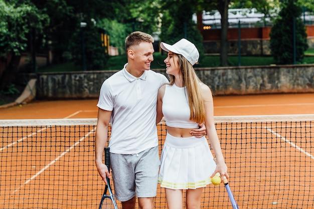 夏に外でテニスのゲームをプレイした後リラックスした若い、かわいいカップル。