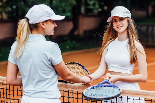 満足している若い女性テニスプレーヤーは、テニスコートでトレーナーと挨拶します。
