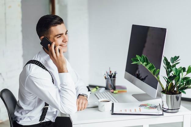 白で隔離、机にコンピューターを持つスタイリッシュな若者。仕事の実業家。