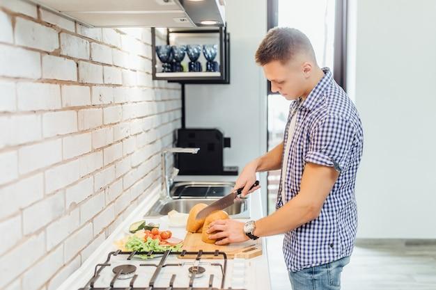 自宅の台所に立って料理をしながら、カジュアルな服装でハンサムな若い男。