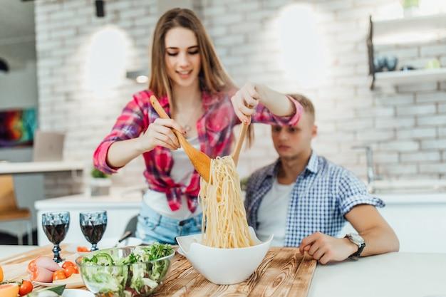 一緒に夕食を準備する陽気な肯定的なパートナーの肖像画、ストーブでマカロニを食べる。