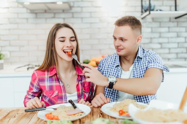 ハンサムな若い男は、モダンな白いキッチンで彼の妻のテイストトマトを与えます。