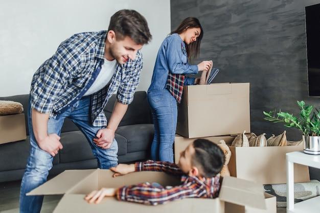 家族は新しい家で段ボール箱を梱包