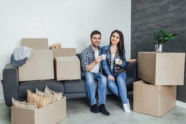 カジュアルな服装の美しいカップルは、彼らの新しい家の計画を議論し、移動のためのボックスの近くのソファに横たわっている間笑顔です。男はコーヒーを飲んでいます。