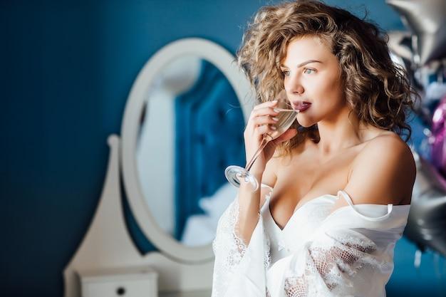 Молодая, улыбающаяся модель с длинными вьющимися волосами празднует в браке с шампанским.