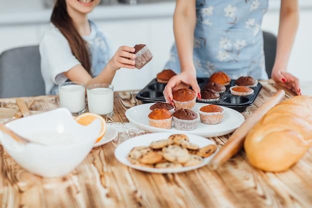 家族がカップケーキとクッキーを一緒に料理する写真