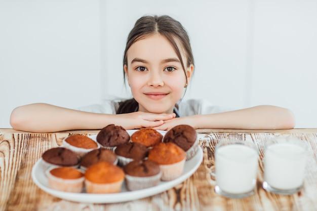かわいい女の子は朝食のカップケーキの時間を持っています