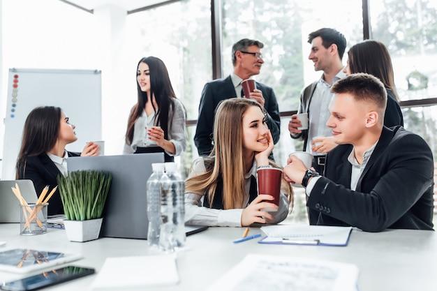オフィスで休憩中の若いビジネス人々のグループ。コーヒーブレークで話している成功するビジネスチーム。