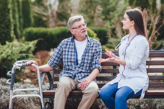 美しい看護師と一緒に公園を歩いて車椅子の親切な高齢女性。
