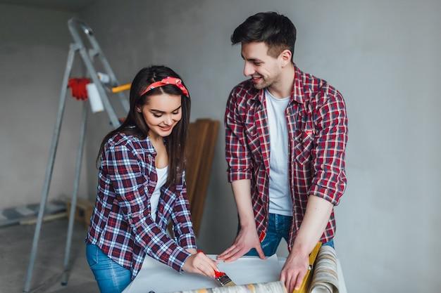 彼らの新しい家を設計する幸せなカップル、彼らは一緒に家のプロジェクトをチェックし、家の改修を行っています