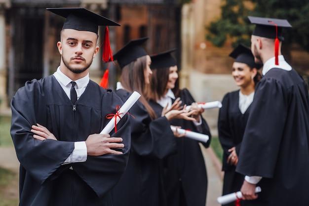 教育、卒業および人々。卒業証書付きの迫撃砲ボードと独身ガウンの幸せな留学生のグループ
