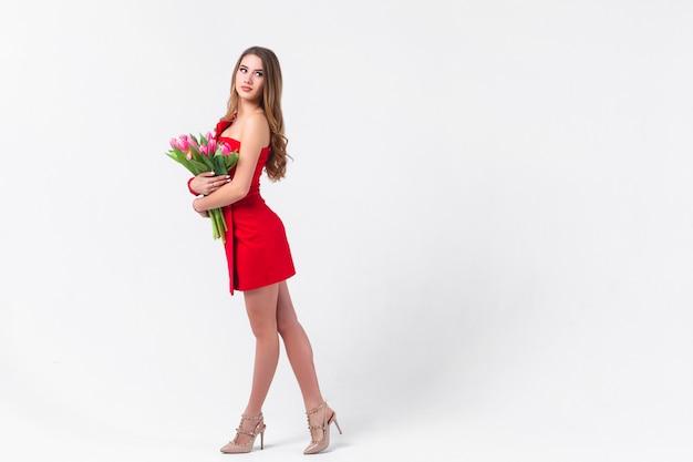 Девушка с тюльпанами в красном положении на сером цвете.