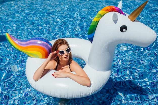 Молодая красивая девушка с красивой фигурой в черном купальнике и солнцезащитных очках