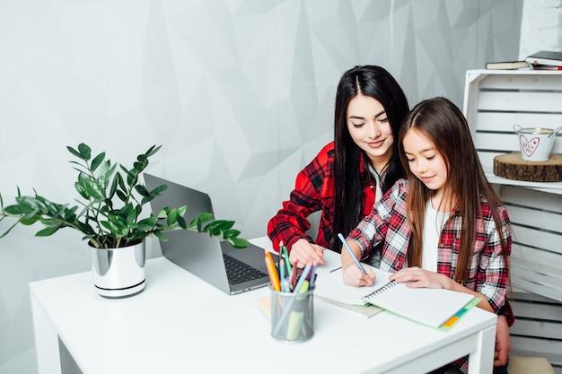 宿題をやっている教育家族と壮大な姉妹レッスン練習試験の準備。