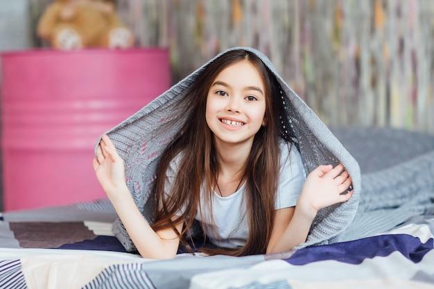寝室で横になっている幸せな少女の肖像画と週末の日があります。