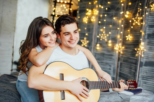 彼らの部屋で美しいカップル。男はギターを弾く