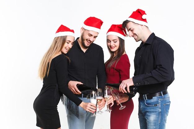 Группа веселых людей в красных шапках наливает шампанское в красивые продукты и празднует новый год