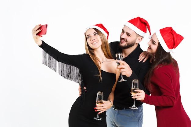 Две красивые девушки и парень в новогодних красных шапках делают сфифи на белом фоне