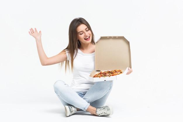 Молодая привлекательная женщина ест кусок вкусной пиццы. у нее футболка, джинсы и кеды, сидящие на полу дома. доставка еды.