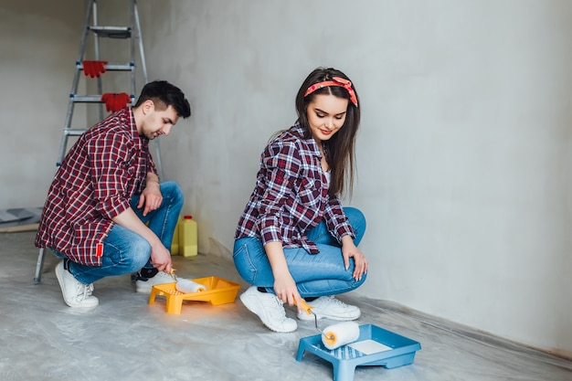 チームワーク、改修および修理の概念、アパートで改装をしている面白いカップルの肖像画