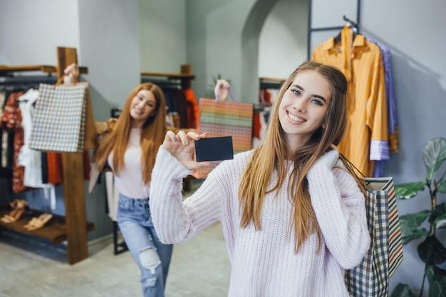 美しいガールフレンドは、クレジットカードでモダンなショッピングセンターを歩いています。