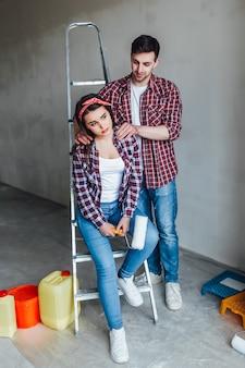 Жена и муж семьи занимаются обустройством дома, мужчина делает для него массаж девушка