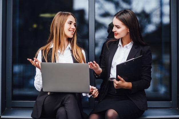 Два межкультурных коллеги в торжественной одежде обсуждают возможные рабочие вопросы перед деловым мероприятием