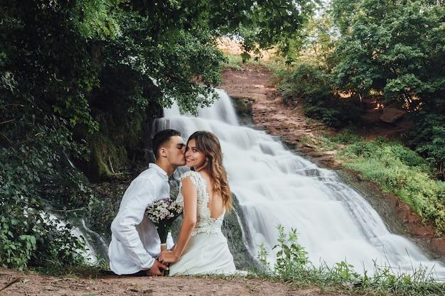 Привлекательные влюбленные с удовольствием отдыхают в горах у водопада на берегу реки.